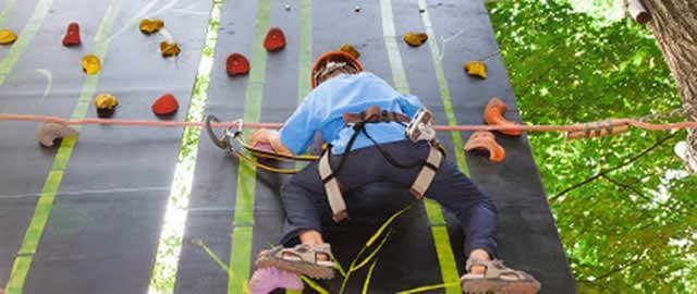 Young boy with equipment climber moves up on climbing wall.